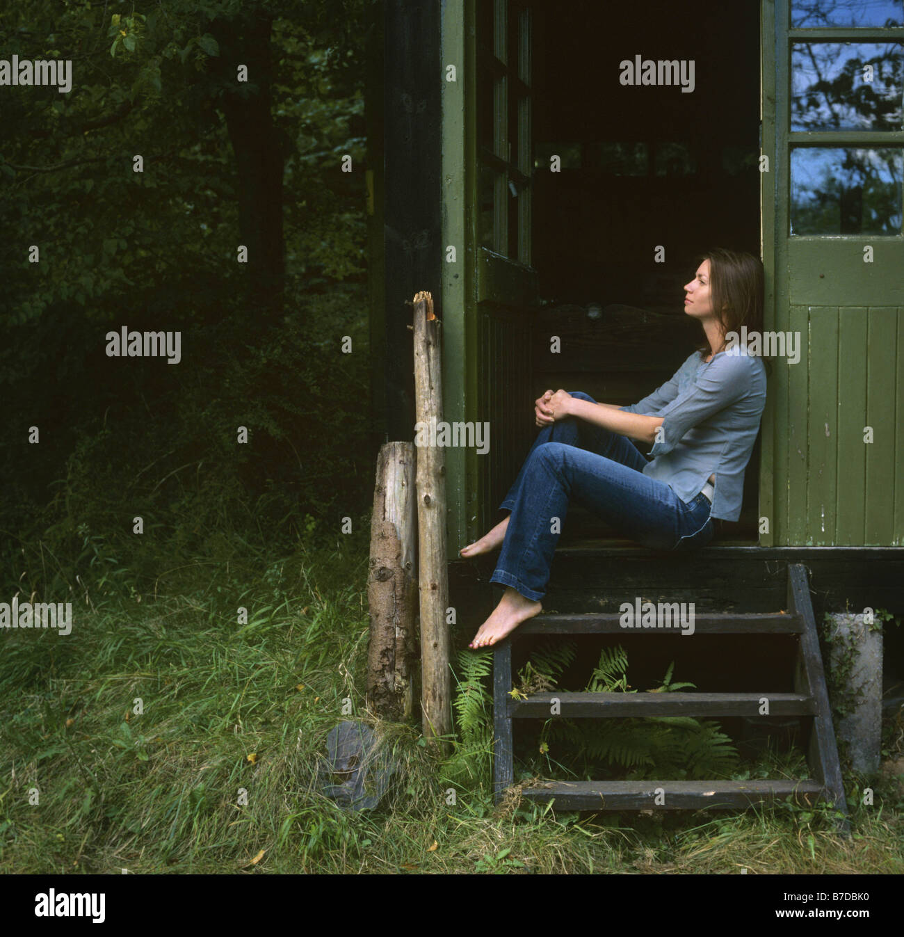 woman relaxing by summer house - Stock Image