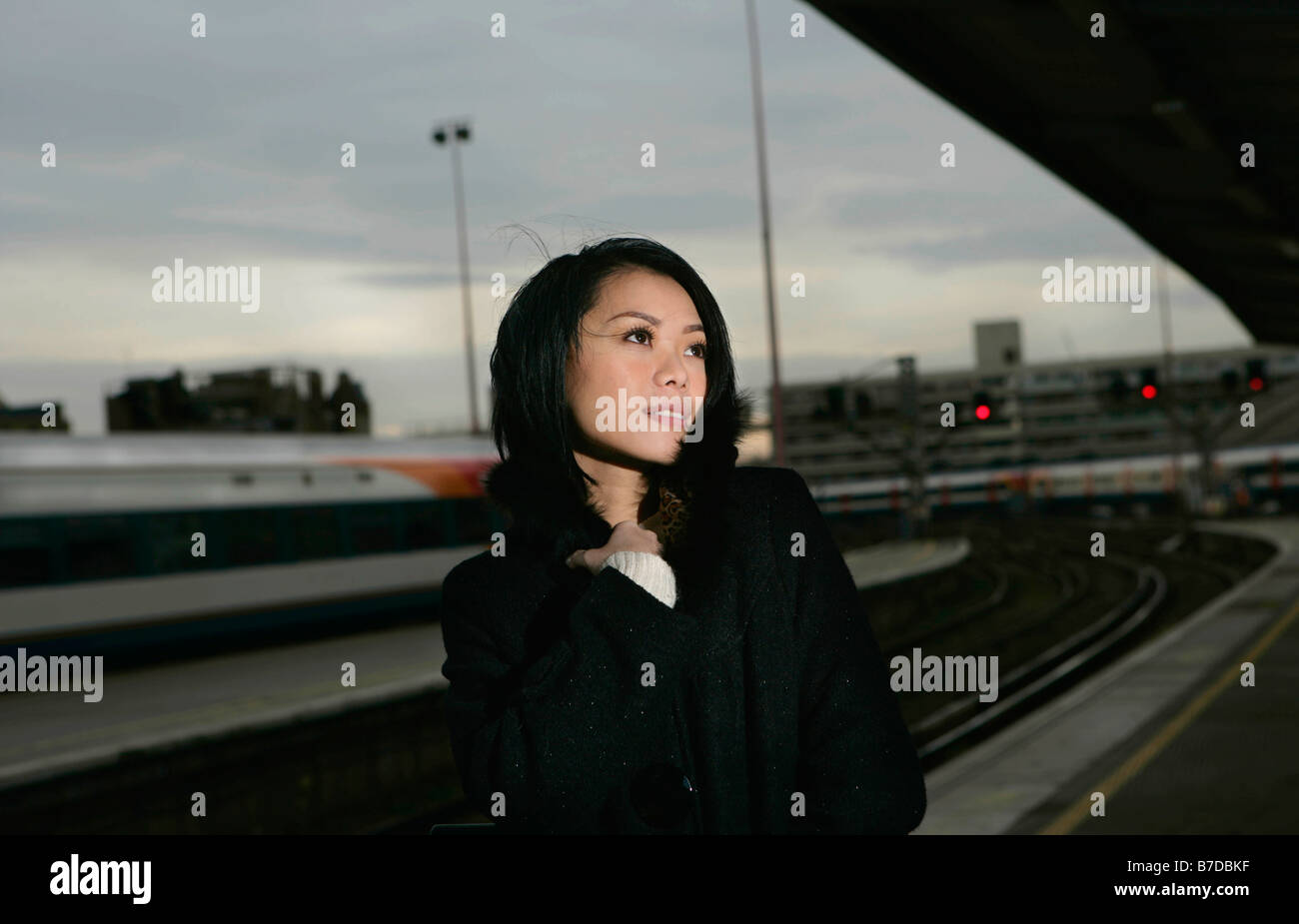 Woman on train platform - Stock Image
