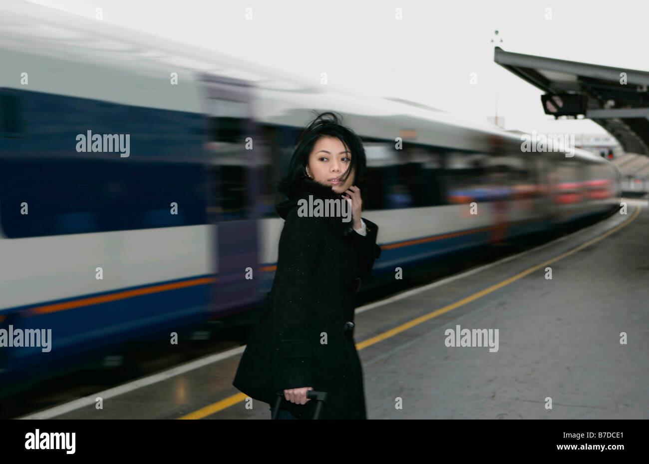 Woman on train platform - Stock Image