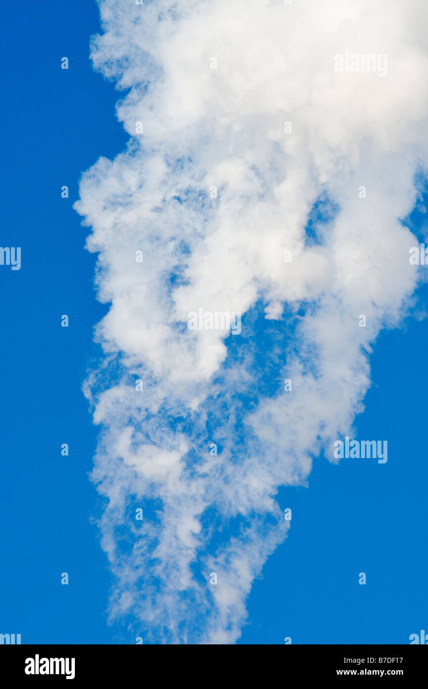 White smoke flowing through a clear blue sky. - Stock Image