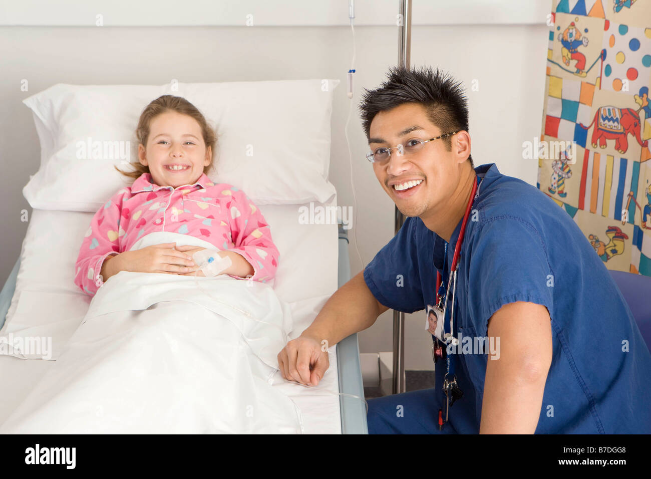 A male doctor visits a sick girl - Stock Image