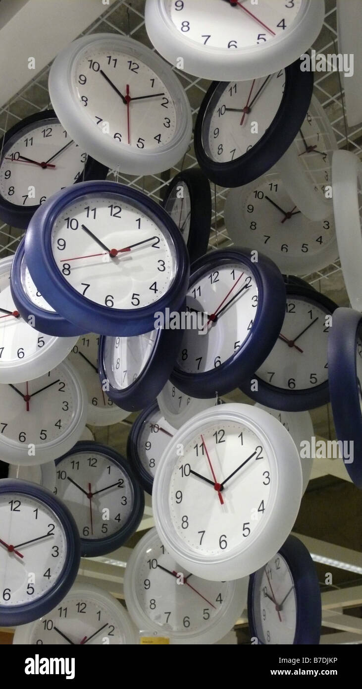 analog wall-clocks hanging down from ceiling - Stock Image