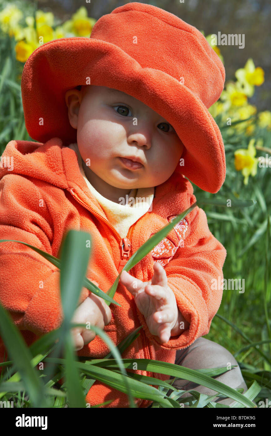Baby wearing red coat and hat sitting in the meadow between yellow flowers. Stock Photo