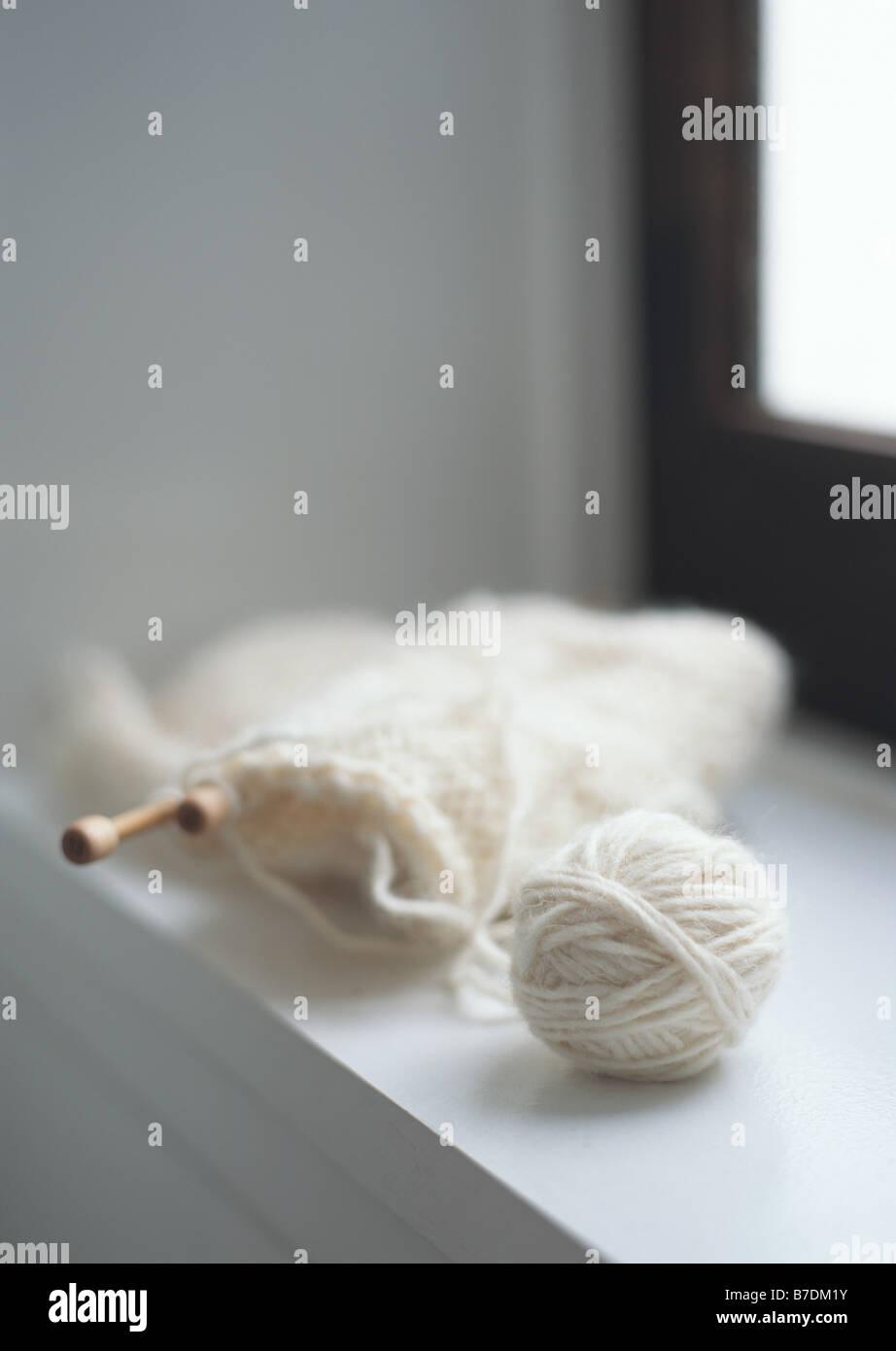 Half-finished white stole on windowsill - Stock Image