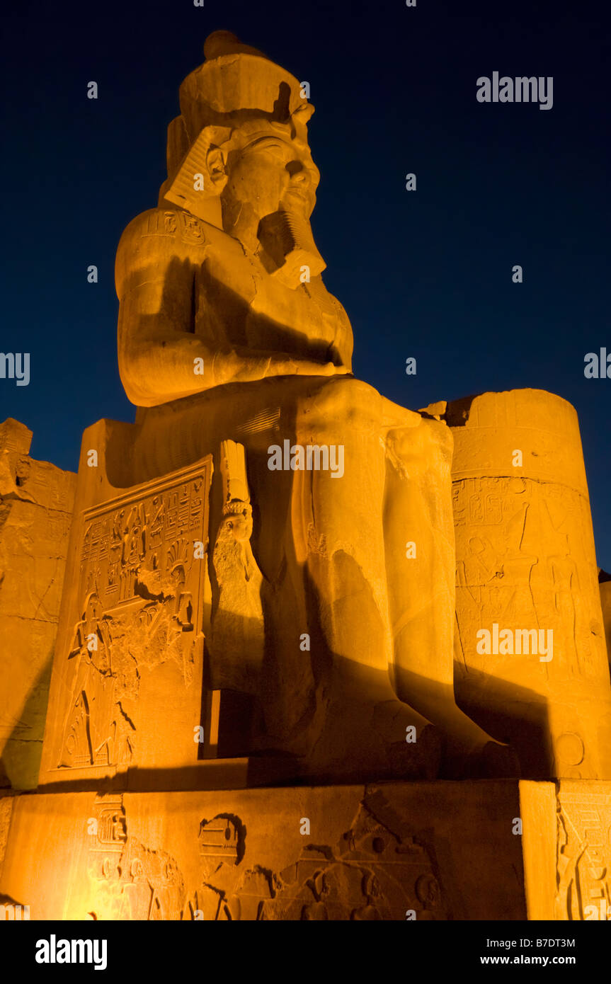 Floodlit statue covered with hieroglyphics inside the Temple of Luxor at sunset Luxor Egypt Middle East - Stock Image