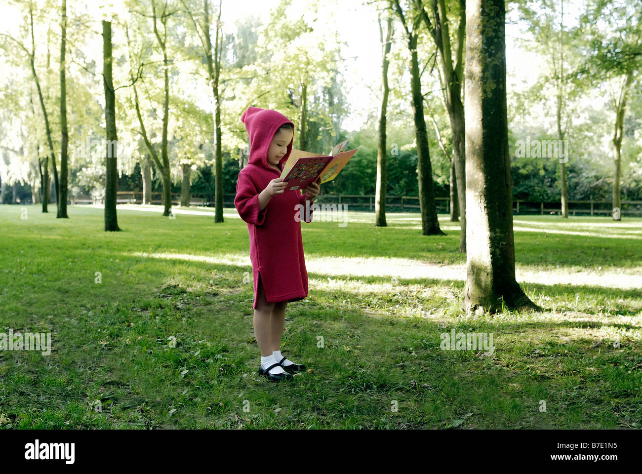 5 years old girl holding a book - Stock Image