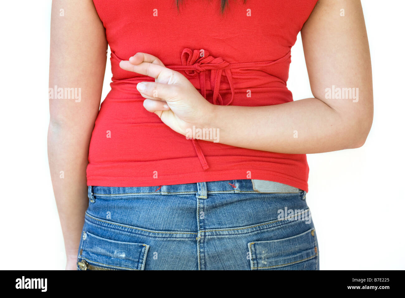 teenage girl seen from behind with her fingers crossed behind her back - Stock Image