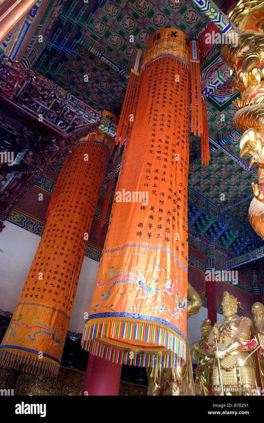 Cylindrical bright-orange silk drape hangs suspended from blue-painted ceiling amidst golden effigies to Chinese Stock Photo