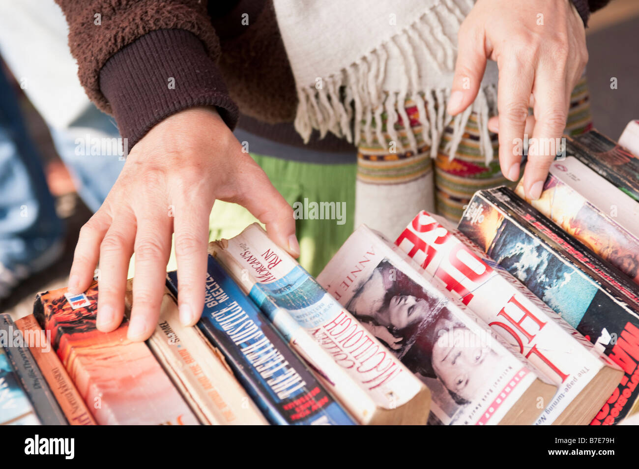 Close Up View Of A Persons Hands Looking Through Used Books On A Second Hand Book Stall Table - Stock Image
