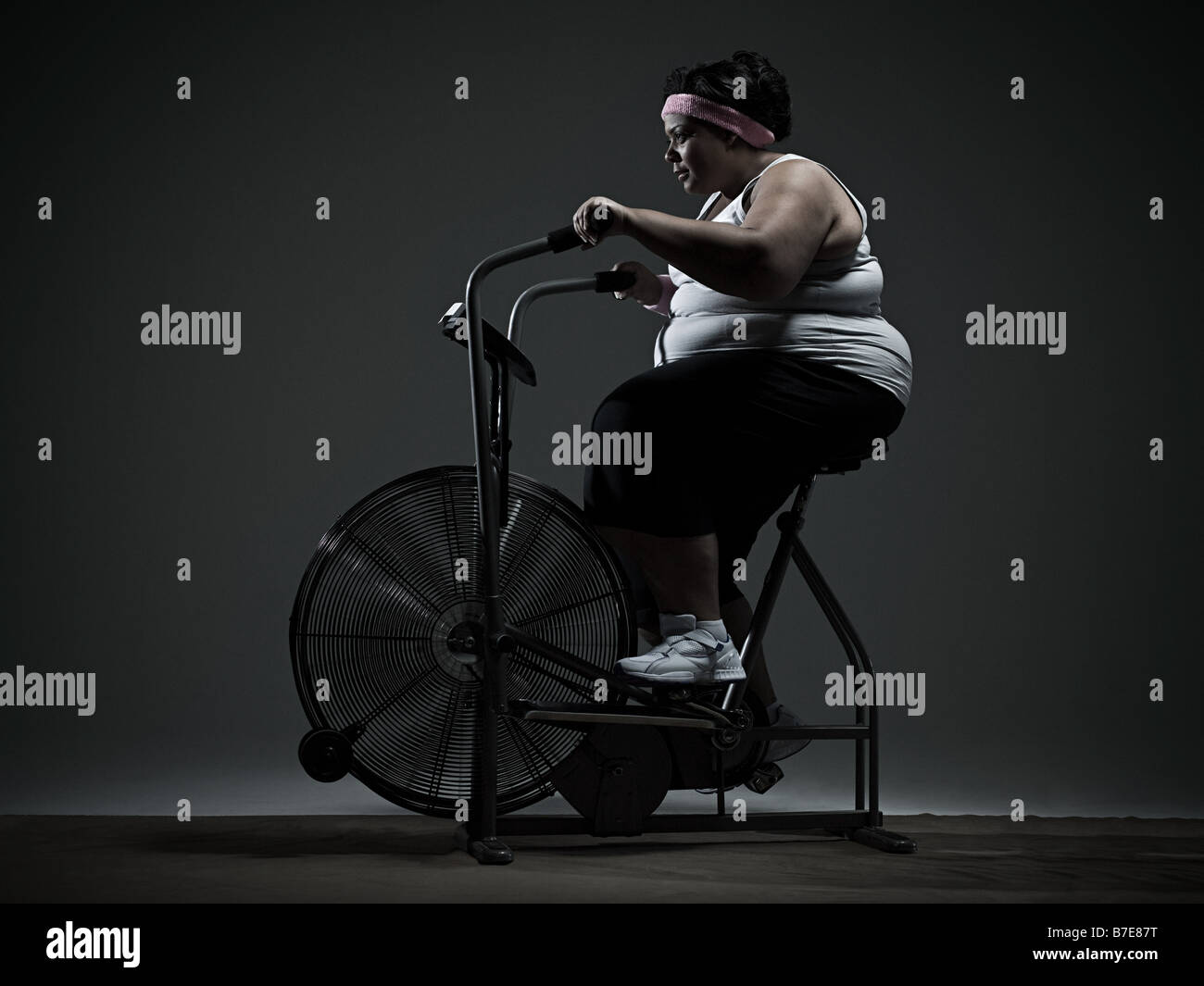 Overweight woman on exercise bike - Stock Image