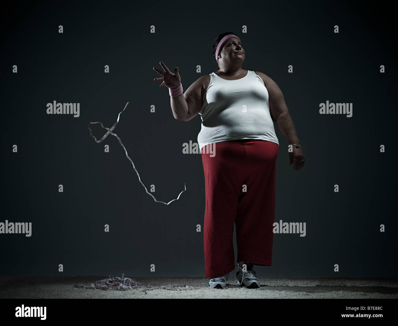 Overweight woman throwing measuring tape - Stock Image