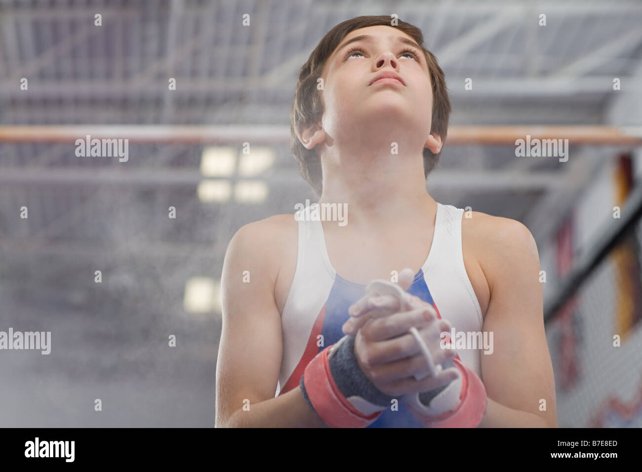 Gymnast rubbing sports chalk onto his hands - Stock Image