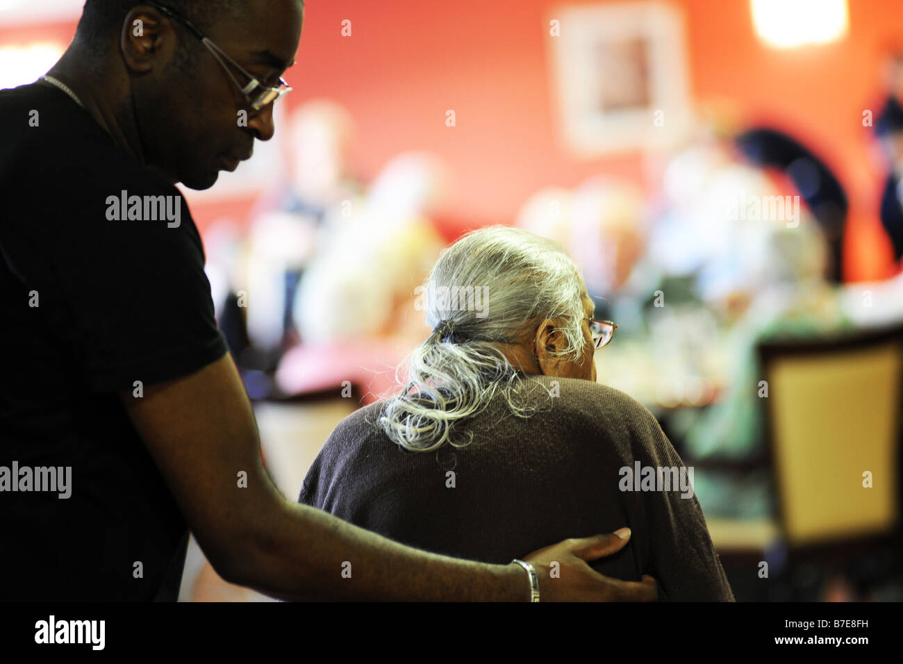 An elderly Sikh lady is helped to her chair in a multicultural extra Care home Bradford West Yorkshire Stock Photo