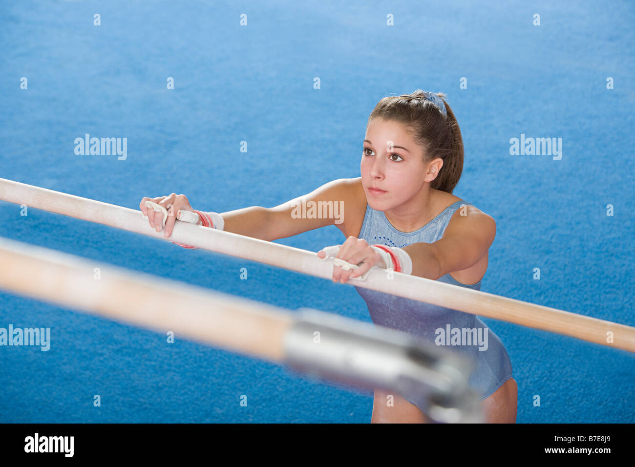 Gymanst holding onto uneven parallel bars - Stock Image