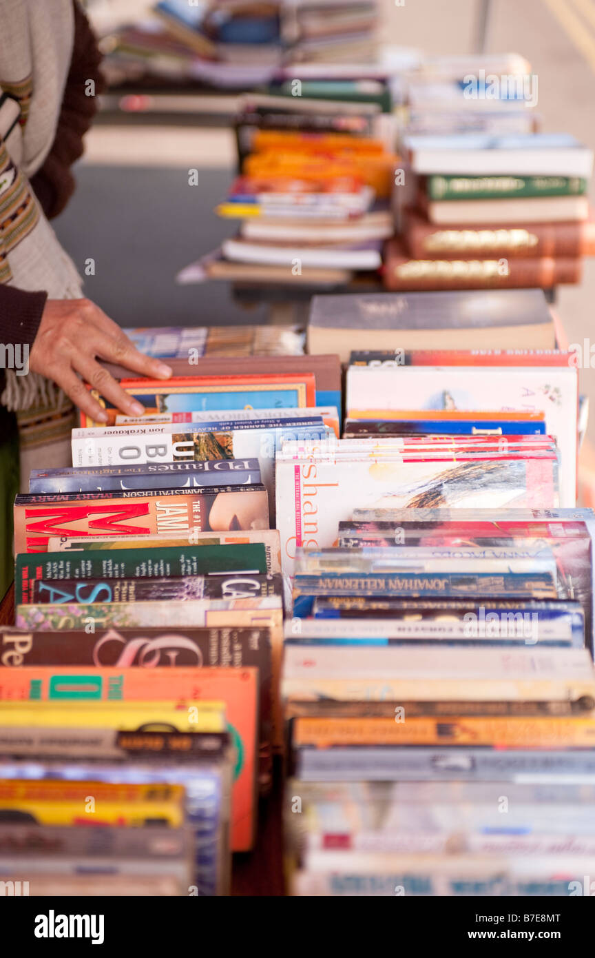 View Of A Persons Hand Taking Used Books Off A Second Hand Book Stall Table - Stock Image