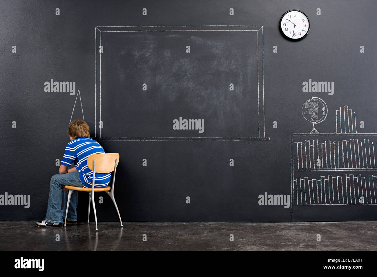 A boy sat in a corner with a chalk dunce cap - Stock Image