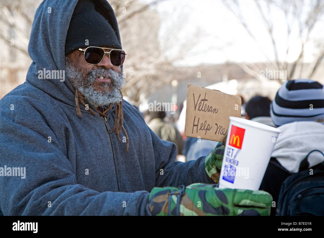 Man Asks Passersby for Handouts - Stock Image