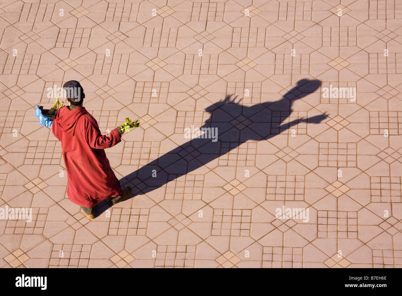 Moroccan man in traditional djellabah selling in Place Djemma el Fna square in the medina in Marrakech, Morocco - Stock Image