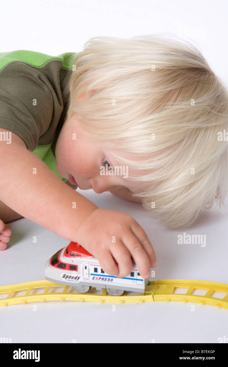 Toddler playing on the floor with a toy train - Stock Image