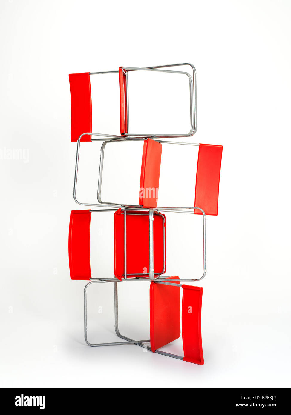 four red folding chairs on top of the other - Stock Image