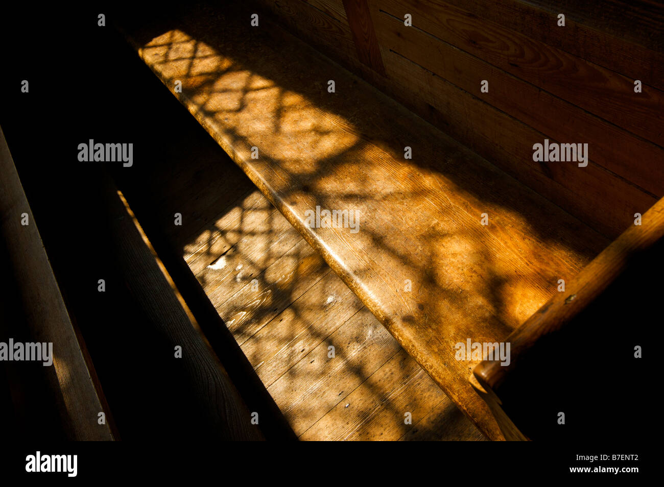 Sunlight form a church window falls on a wooden pew - Stock Image