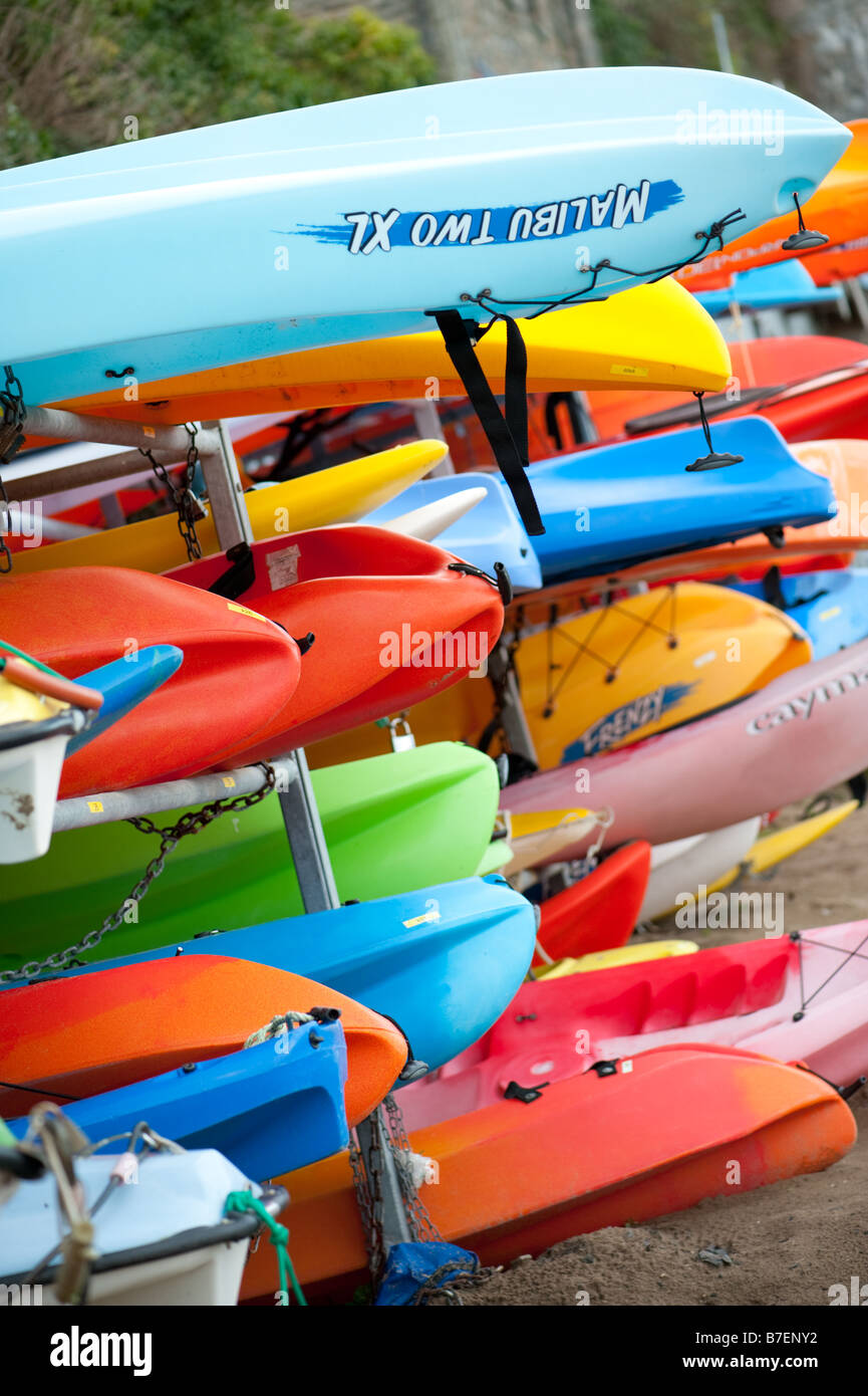 Racks of brightly coloured kayaks and canoes at New Quay Ceredigion Wales UK - Stock Image