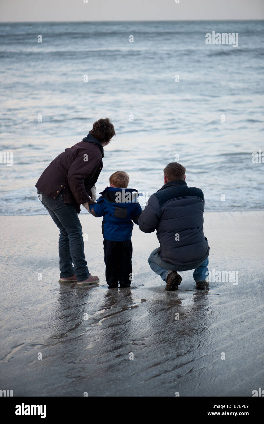 Young family on the beach at New Quay Ceredigion west wales on a winter afternoon dodging the waves, UK - Stock Image