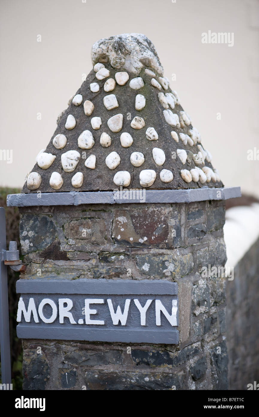 Gate post to a house Mor Ewyn 'sea spray' in Aberaeron Ceredigion Wales UK decorated with white pebbles - Stock Image