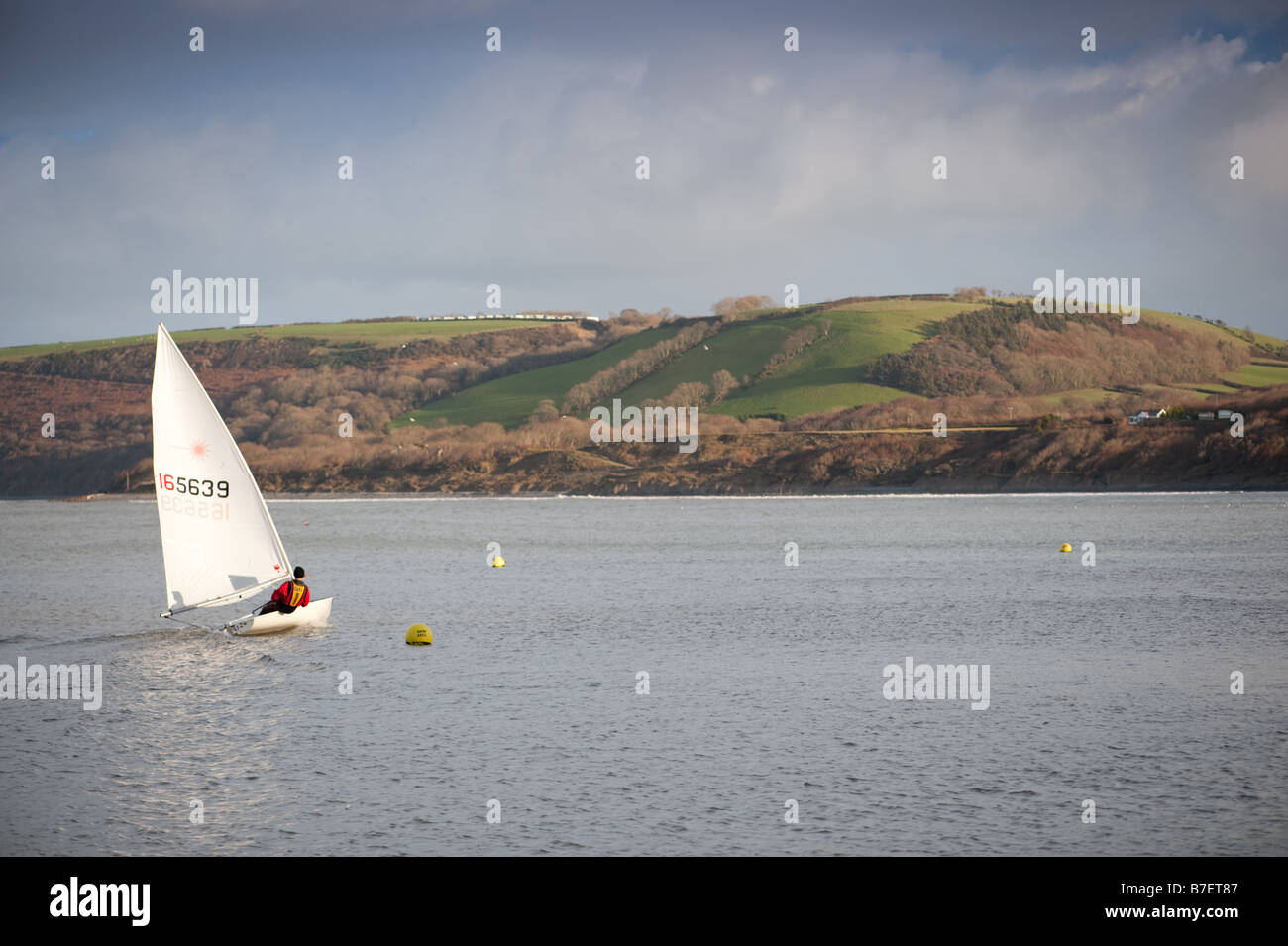 Winter afternoon A man sailing his small dinghy in the sea off New Quay Ceredigion Wales UK - Stock Image