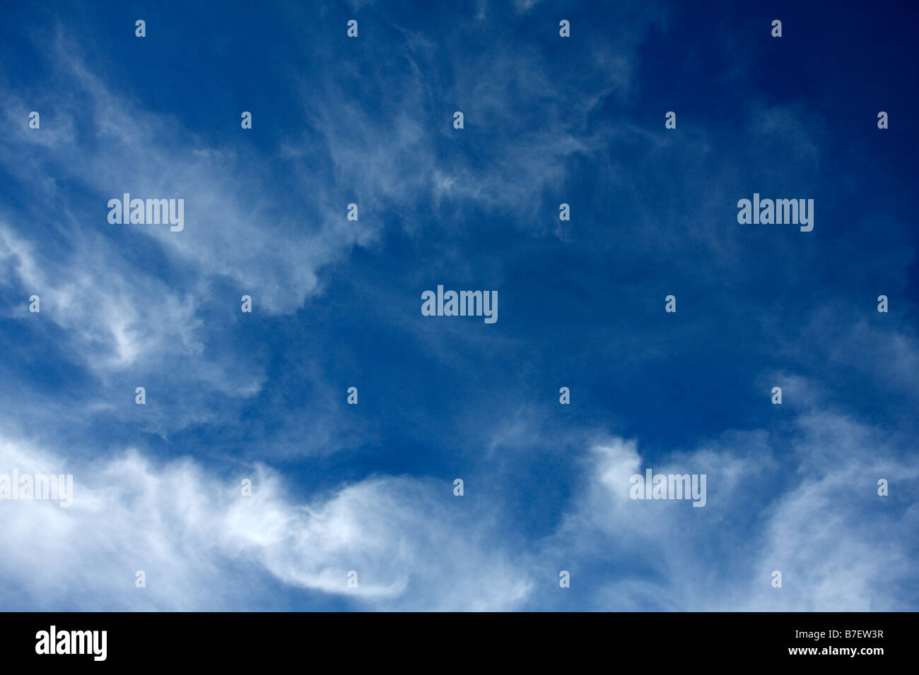 Blue sky and wispy stratocirrus or cirrus clouds. - Stock Image