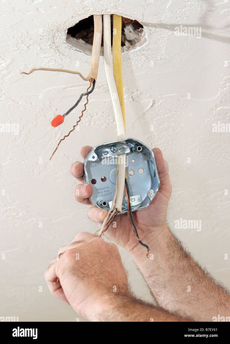 an electrician threading wire through a regulation fan ceiling box work  being performed to code by