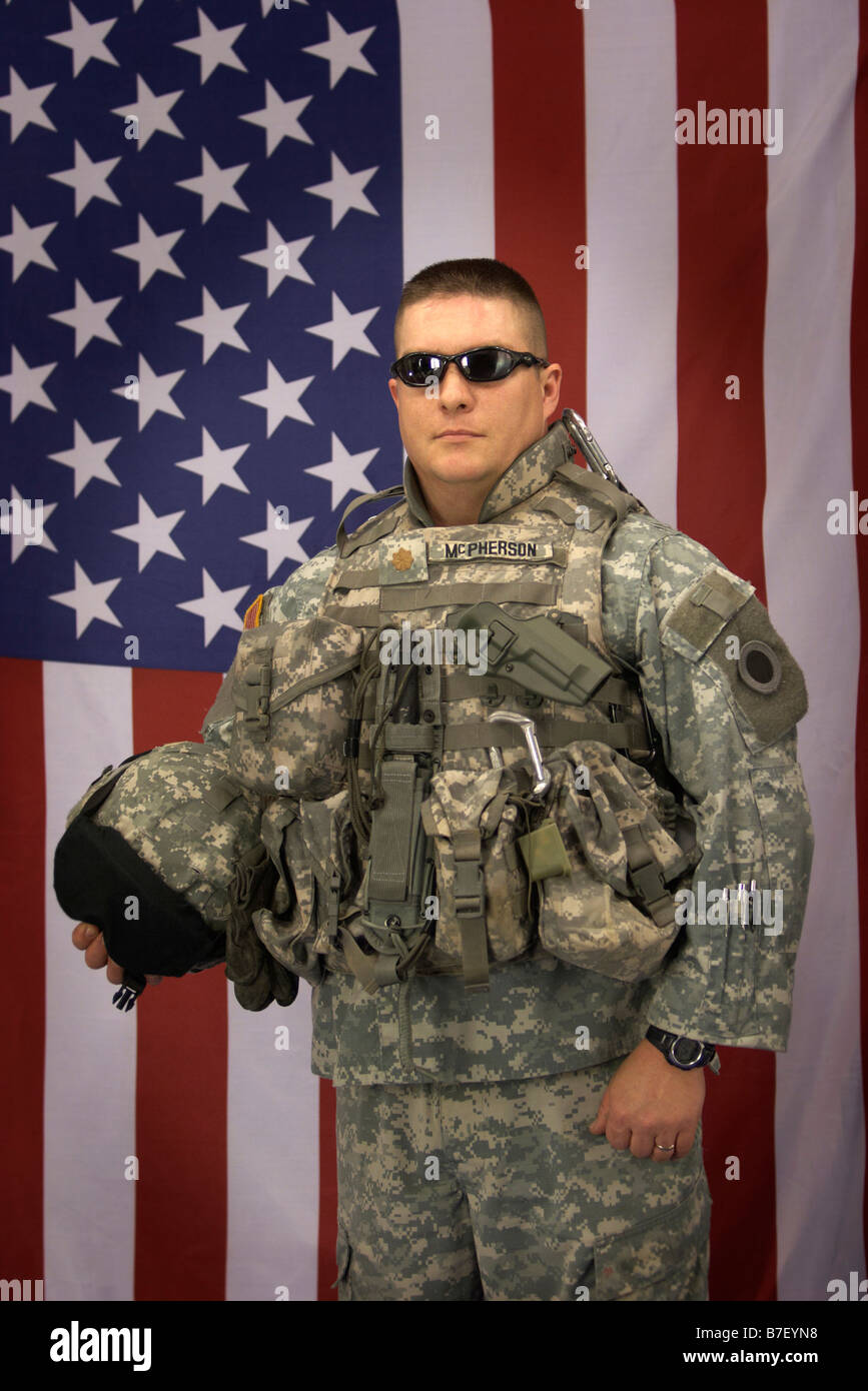 A United States Army officer in front of an American Flag in uniform - Stock Image