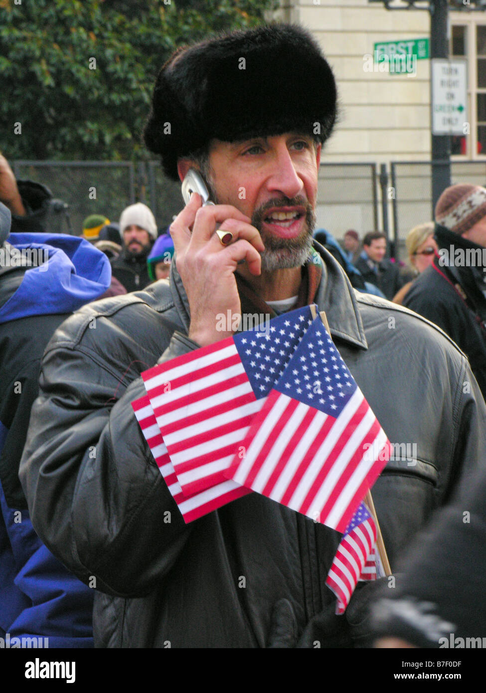 A white man holds flags and talks on his cellphone in the crowd at Barack Obama's inaugruation as America's - Stock Image
