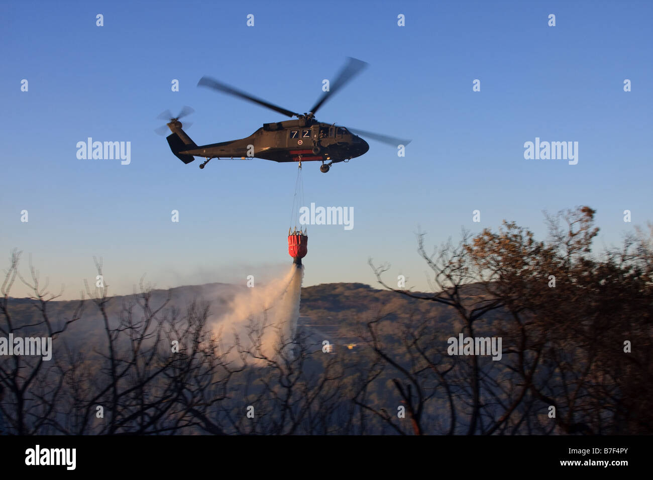 Sikorsky UH-60 Black Hawk helicopter dumping water on a fire. - Stock Image