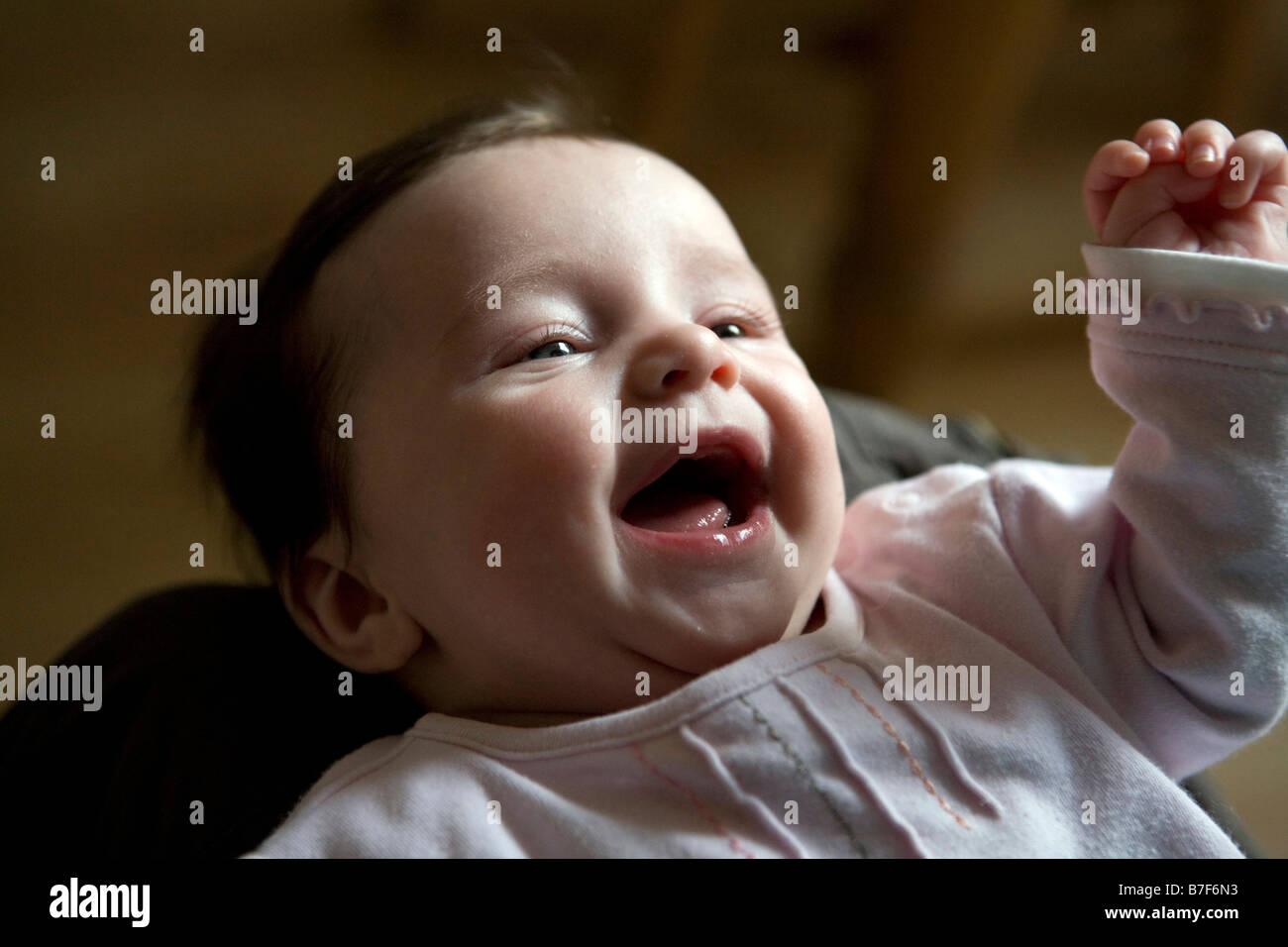 A baby girl laughing with joy - Stock Image