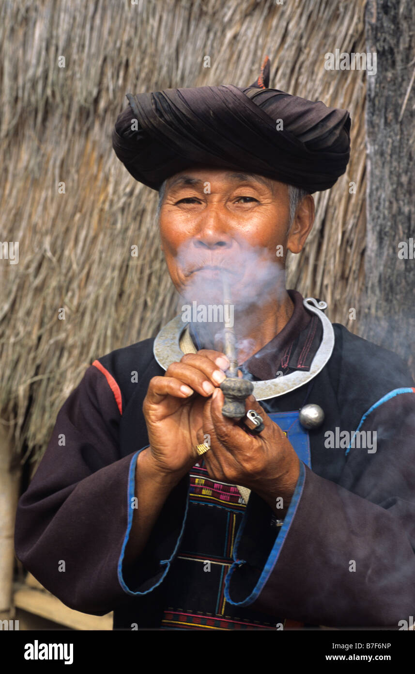 Portrait of Akha Man from northern Thai Hill Tribe Smoking Opium Pipe, near Chiang Rai, northern Thailand - Stock Image