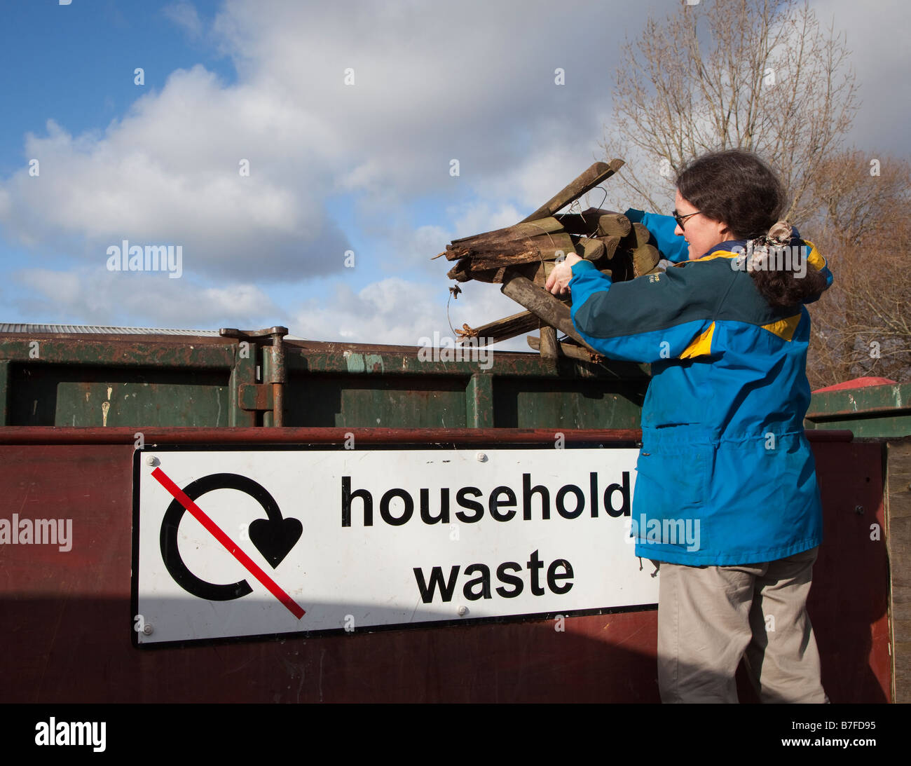 Woman throwing away rotten wood into household waste skip at recycling yard Wales UK - Stock Image