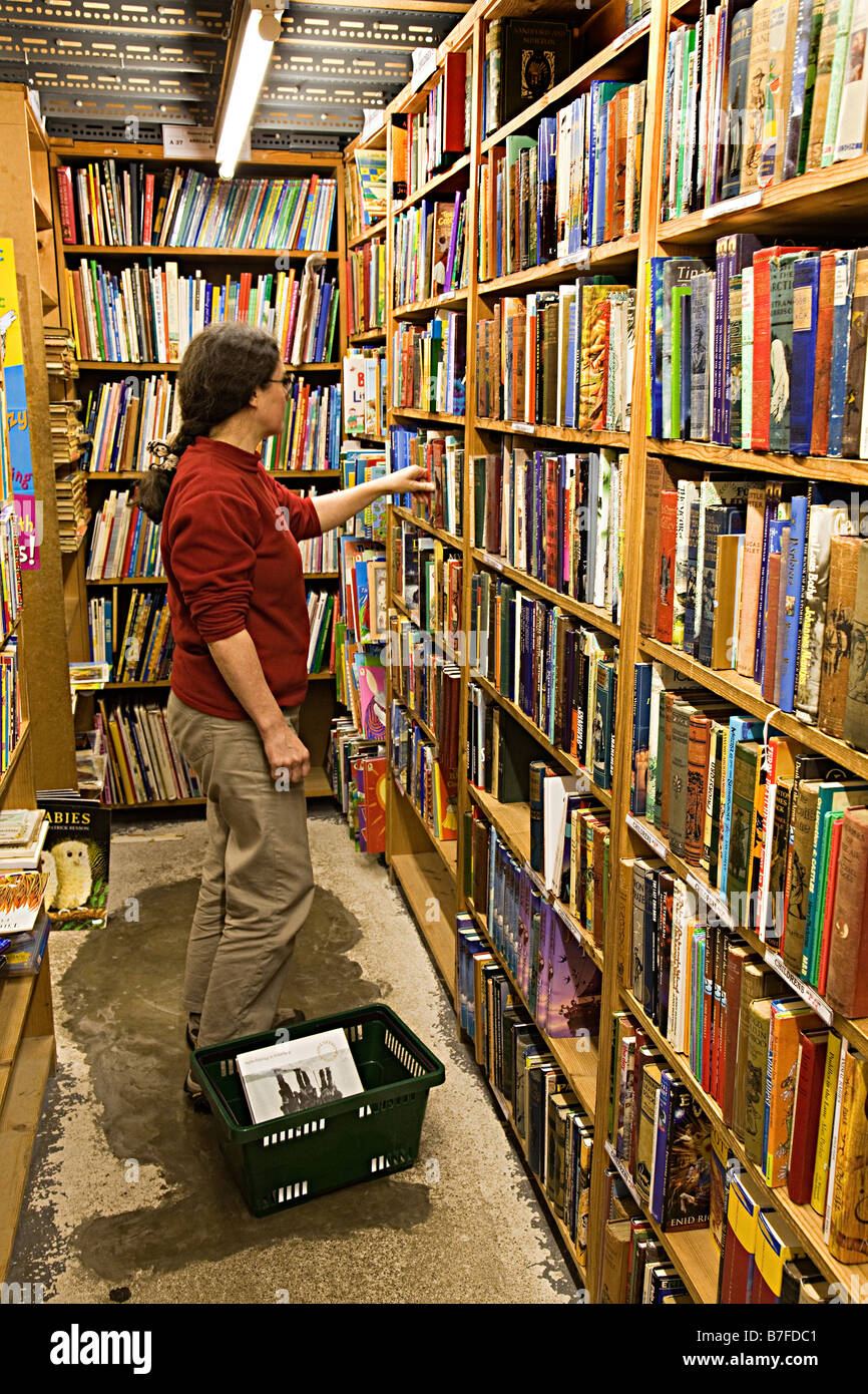 Woman browsing second hand books on shelves in bookshop Hay on Wye UK - Stock Image