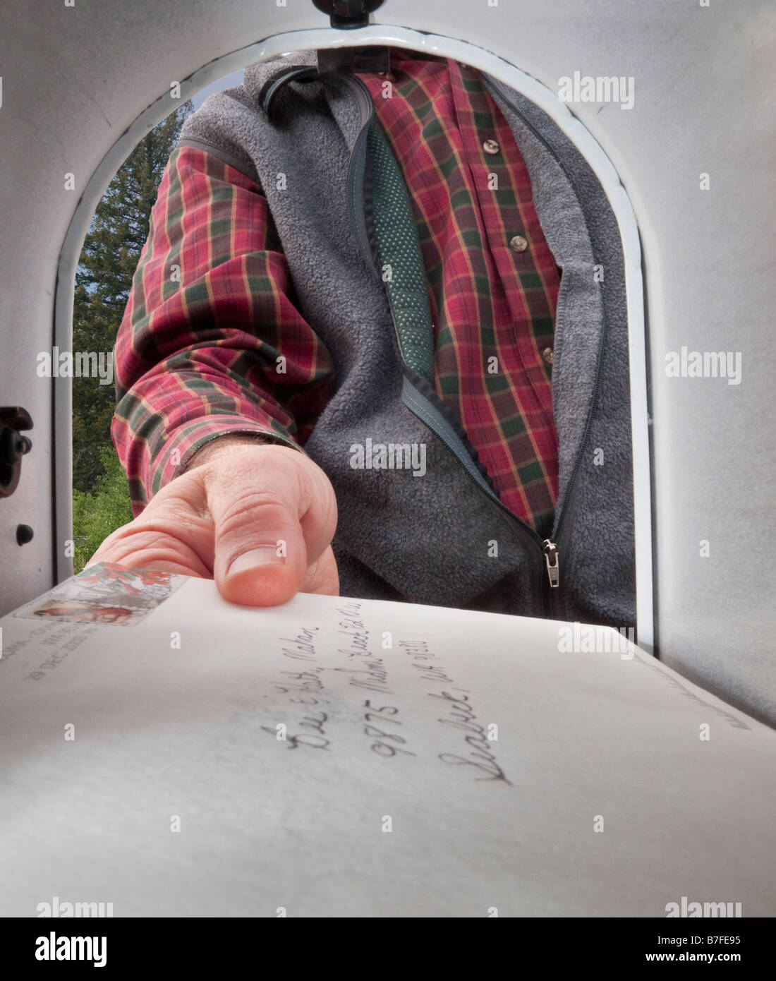 Picking up mail from the letter's perspective inside the mailbox Stock Photo