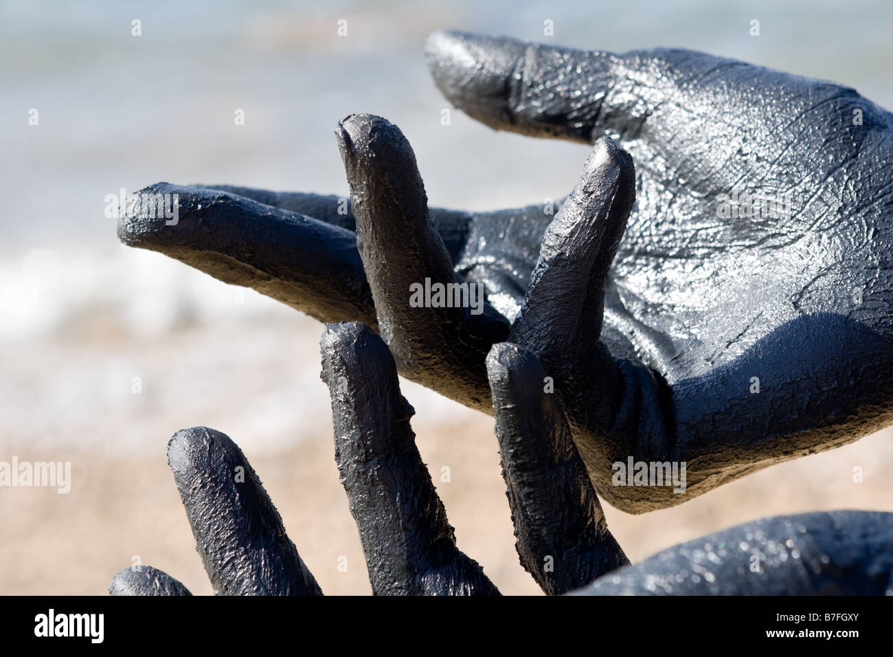 Hand covered with mud from Dead sea Jordan Skincare treatment Use of high depth of field to blur the background - Stock Image