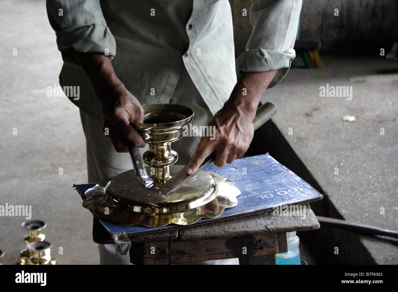 A black smith working on brassware in Terengganu, Malaysia. - Stock Image