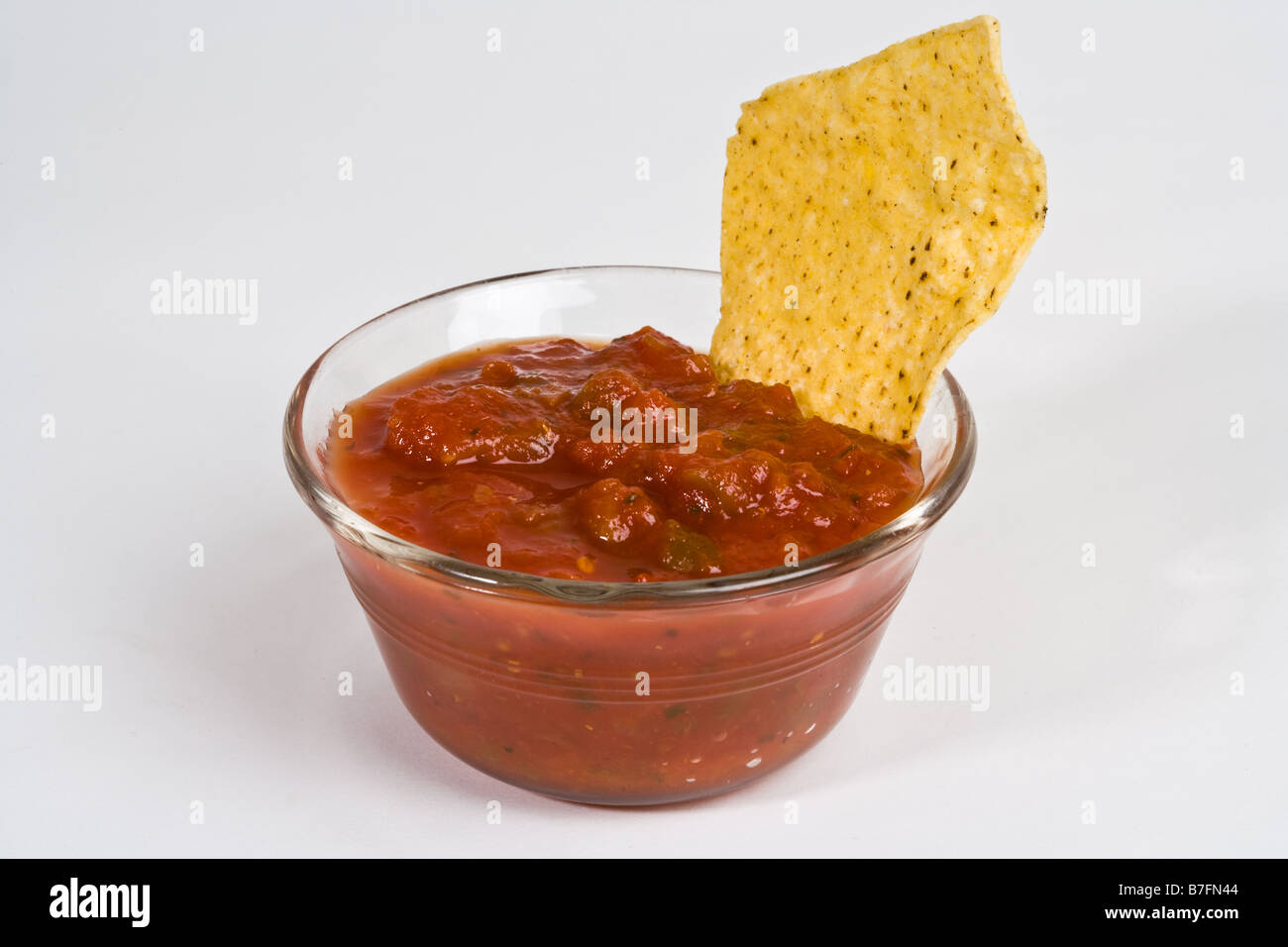 A corn chip dipped in a bowl of salsa - Stock Image
