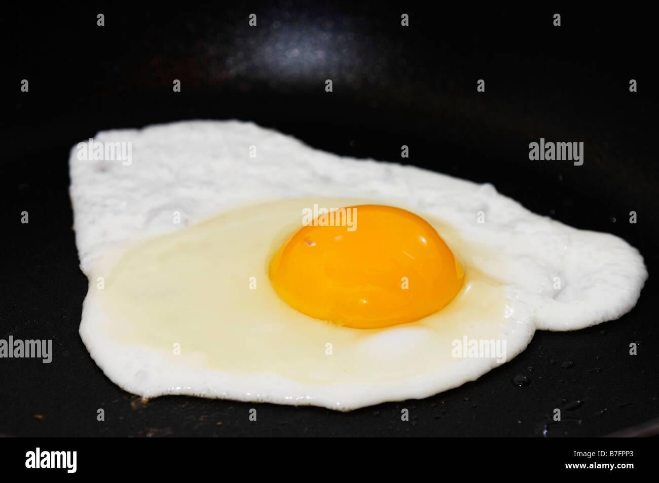 food fried egg on teflon pane - Stock Image