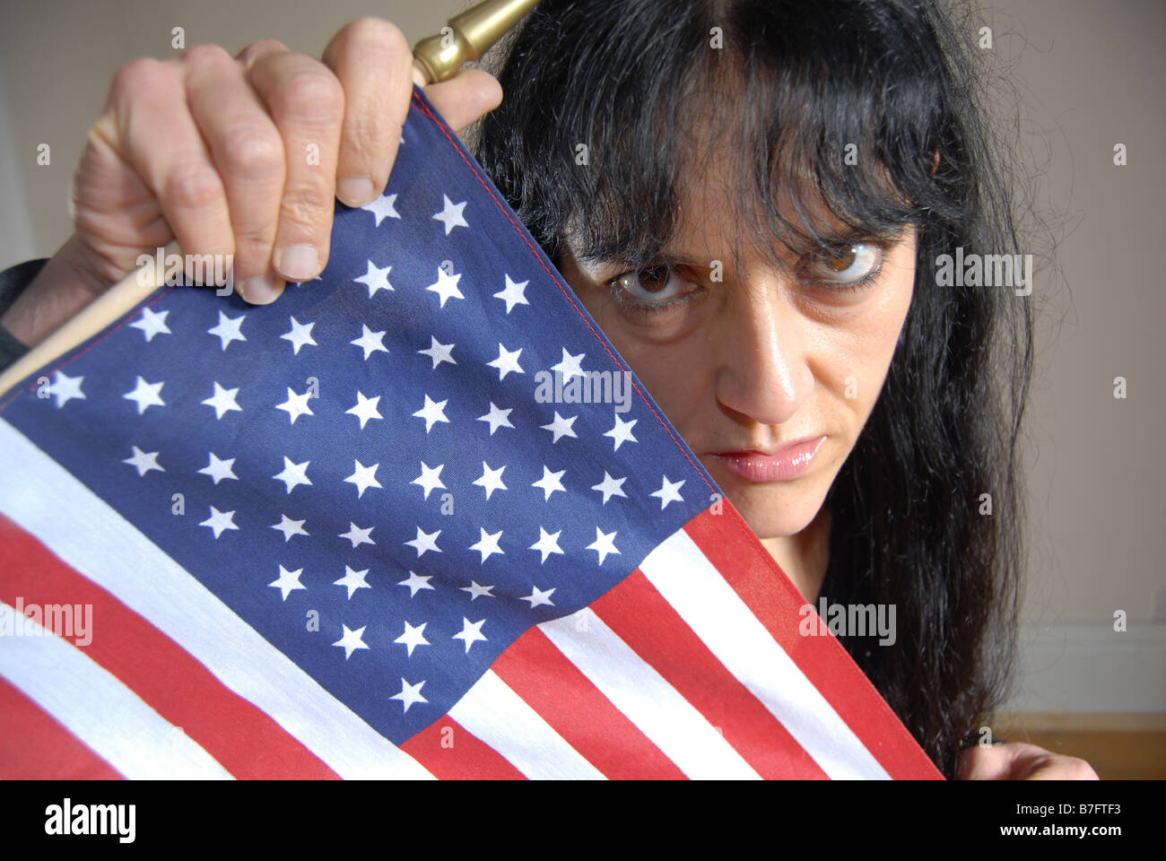 A no nonsence woman with black hair holding the American Stars & Stripes - Stock Image