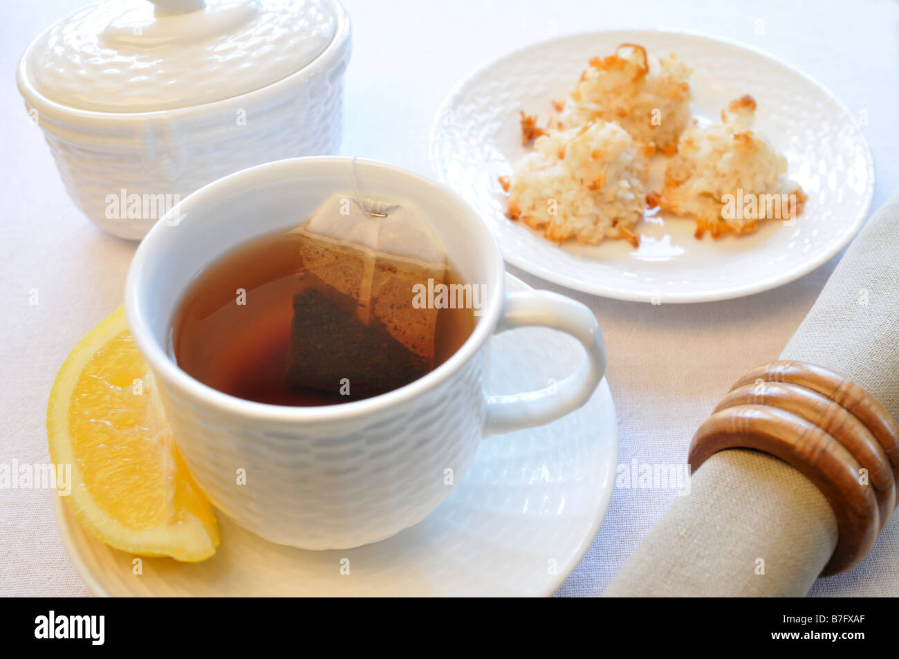 Black tea in cup with lemon coconut macaroon cookies napkin and sugar bowl on table - Stock Image