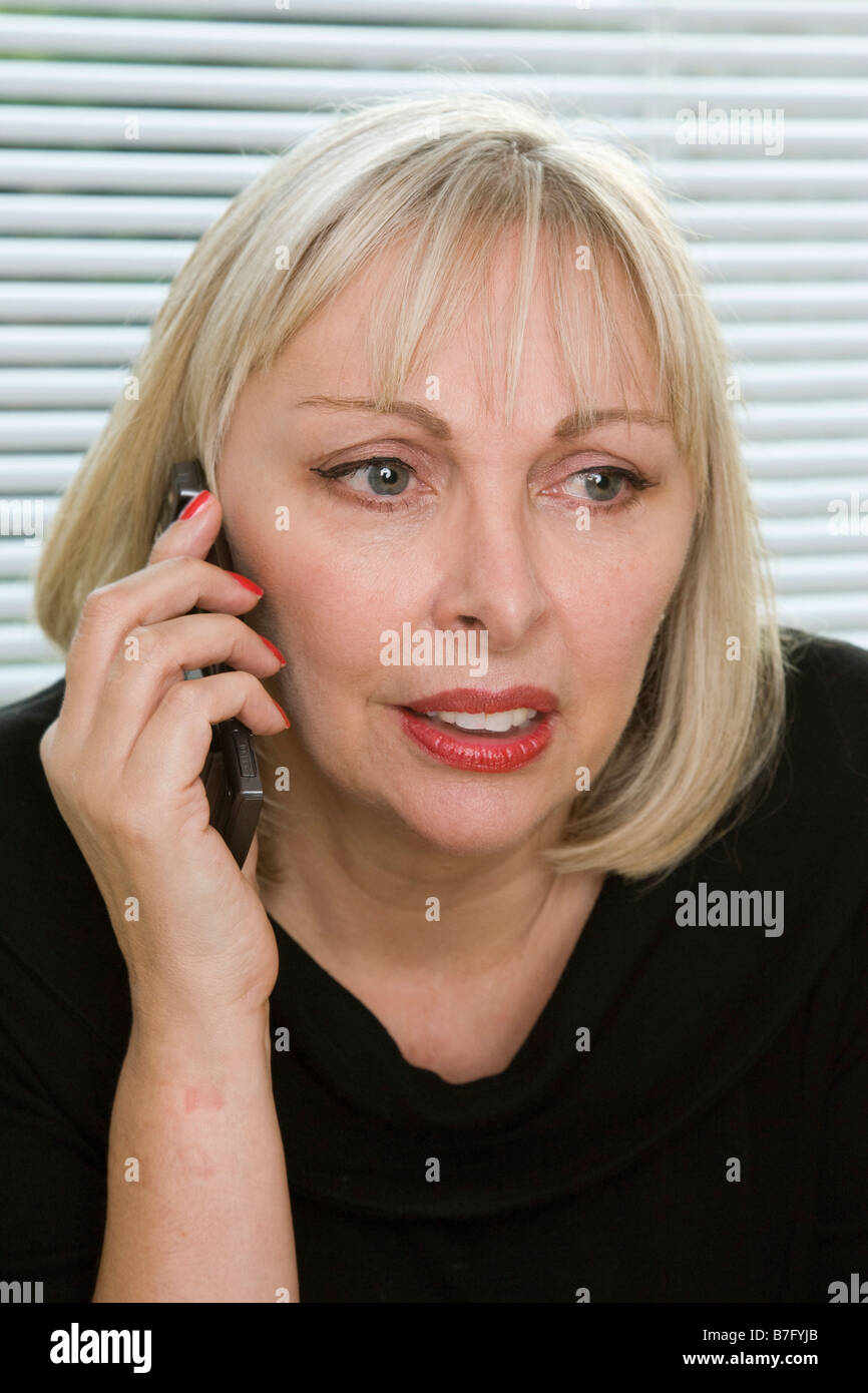 worried woman chatting on phone - Stock Image