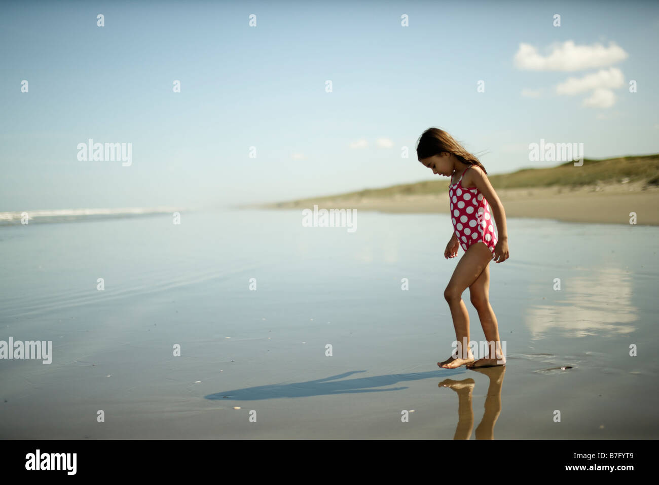 Himatangi beach New Zealand, five year old girl plays in sea - Stock Image