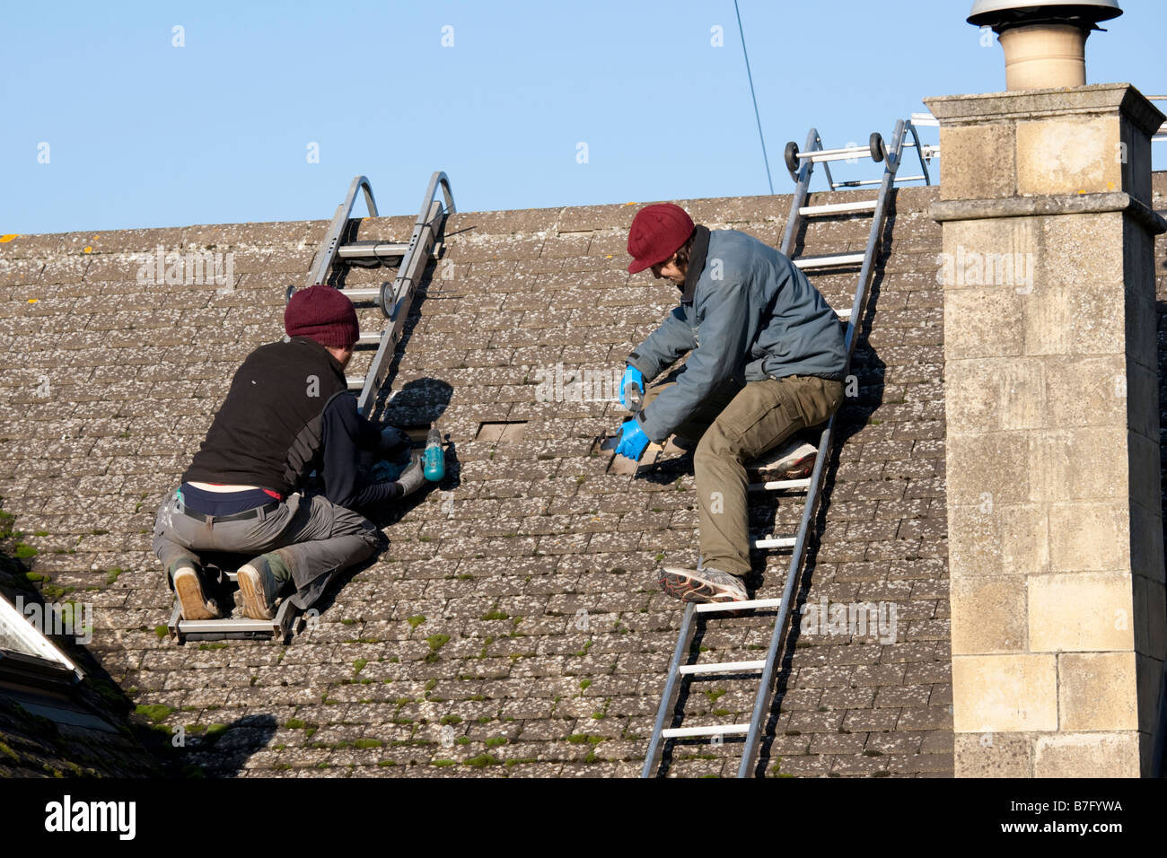 Installing solar thermal evacuated tubes on tiled roof Cotswolds UK - Stock Image