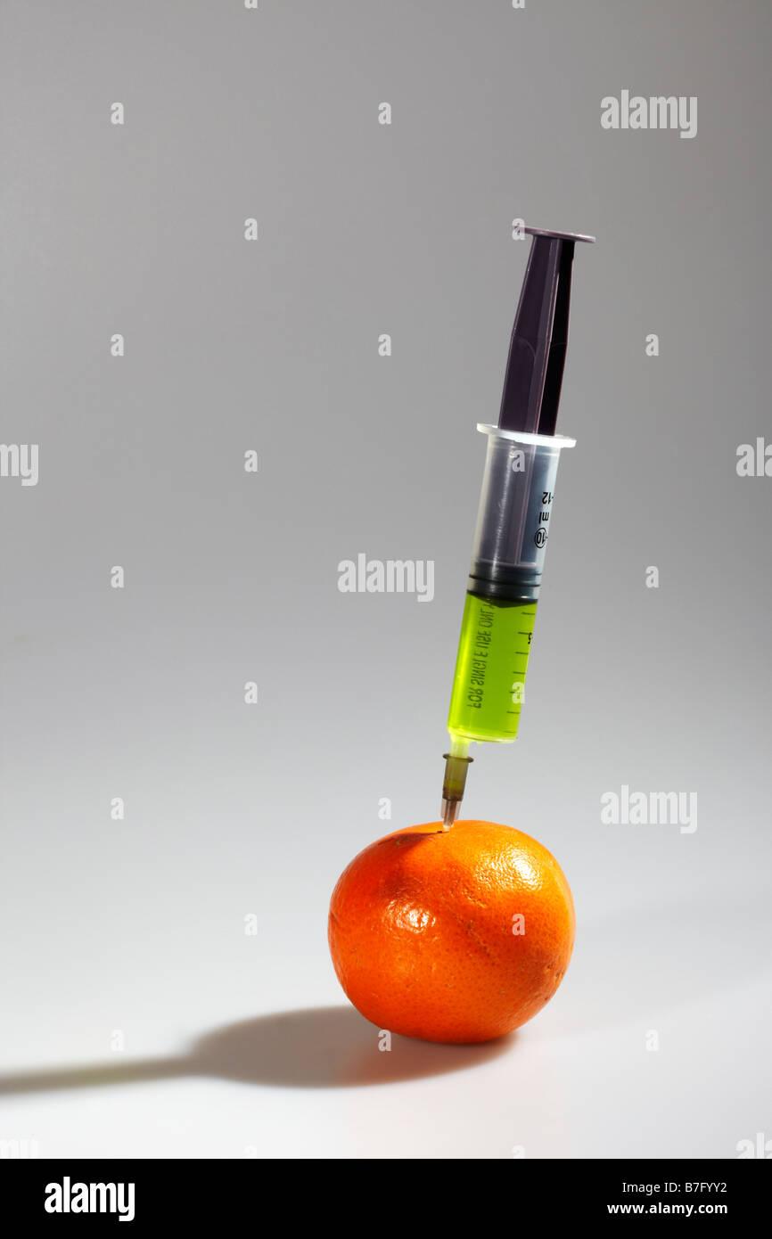 Hypodermic Syringe and Orange - Stock Image
