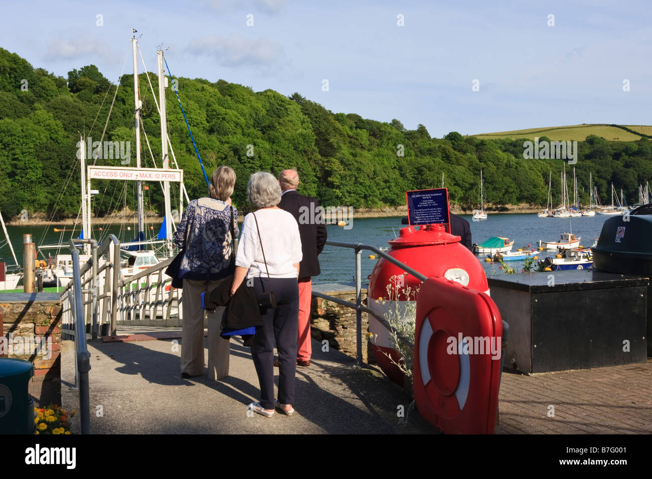 Visitors returning to their yacht survey the River Fowey - Stock Image
